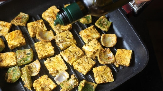 drizzling oil on paneer tikka