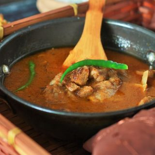 Mutton-Masala-Recipe with a wooden spoon in a kadai