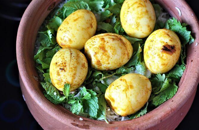 egg placed on rice for preparing dum for egg biryani