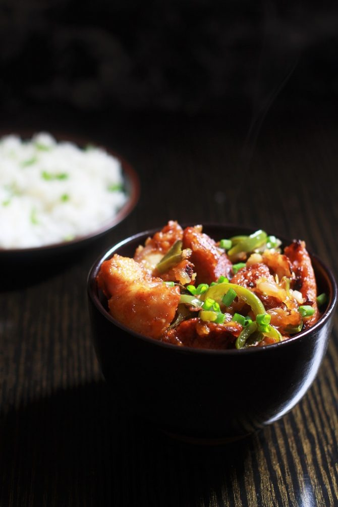 Chicken Manchurian Dry Recipe in a bowl with rice in a plate at the background
