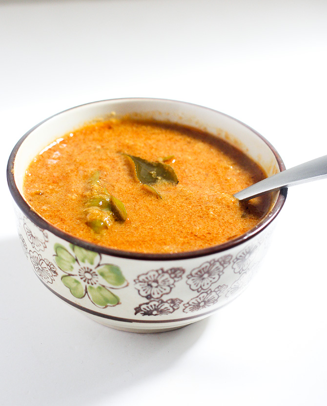 Chettinad Onion Kulambu served in a bowl with spoon
