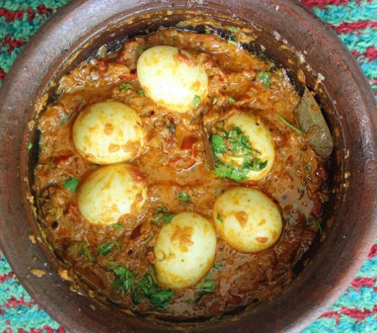 overhead view of egg korma recipe in a clay pot