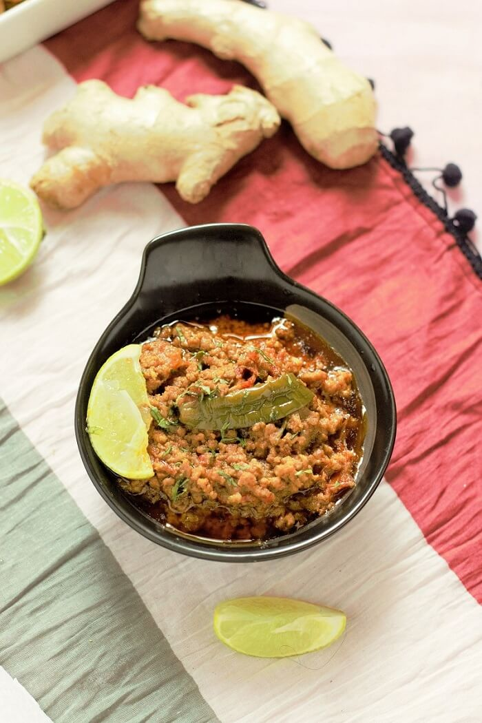 mutton keema recipe in a black bowl with lemon wedge